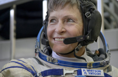 astronaut Peggy Whitson smiles as she listens to a reporter's question